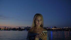 Mulher bonita que usa o telefone na terraplenagem do por do sol video estoque
