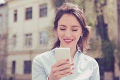 Mulher bonita que usa seu telefone celular na rua Foto de Stock Royalty Free