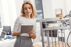 Mulher bonita que usa sua tabuleta quando funcionamento da impressora 3D Imagens de Stock