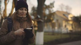 Mulher bonita que usa a tecnologia esperta app do telefone que anda com o movimento lento de vida do estilo de vida feliz urbano  video estoque