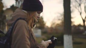Mulher bonita que usa a tecnologia esperta app do telefone que anda com o movimento lento de vida do estilo de vida feliz urbano  vídeos de arquivo