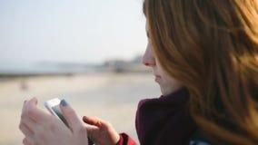 Mulher bonita que usa a tecnologia esperta app do telefone em ruas da cidade no dia ensolarado frio filme