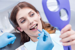 Mulher bonita que verifica os dentes após ter curado os dentes na clínica dental imagens de stock royalty free