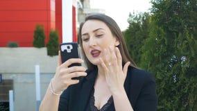 Mulher bonita que verifica seus composição e cabelo usando o smartphone antes de tomar o selfie video estoque