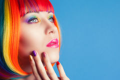 Mulher bonita que veste a peruca colorida e que mostra pregos coloridos Imagem de Stock Royalty Free