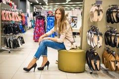 Mulher bonita que veste sapatas novas dos saltos altos na loja Foto de Stock