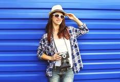 Mulher bonita que veste um chapéu de palha, óculos de sol, camisa quadriculado com câmera retro Fotografia de Stock Royalty Free