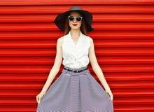 Mulher bonita que veste um chapéu de palha preto, óculos de sol Fotografia de Stock Royalty Free