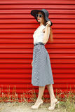 Mulher bonita que veste um chapéu de palha preto, uns óculos de sol e uma saia listrada sobre o vermelho fotografia de stock royalty free