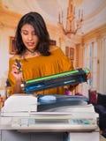Mulher bonita que veste uma blusa marrom que fixa uma fotocopiadora e que sorri durante a manutenção usando uma chave de fenda Fotos de Stock Royalty Free