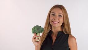 Mulher bonita saudável alegre que guarda os brócolis, mostrando os polegares acima video estoque