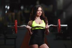 A mulher bonita saudável do ajuste guarda um barbell nas mãos foto de stock royalty free