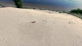 A mulher bonita saudável, nova nos óculos de sol que meditam, esticando, ioga praticando na praia do mar, no nascer do sol, faz vídeos de arquivo