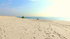 A mulher bonita saudável, nova nos óculos de sol que meditam, esticando, ioga praticando na praia do mar, no nascer do sol, faz video estoque