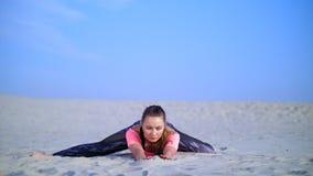 A mulher bonita saudável, nova que estica, ioga praticando na praia, no nascer do sol, faz exercícios para o equilíbrio e video estoque