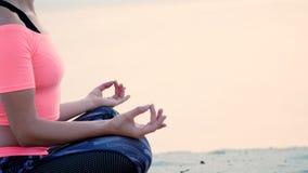 A mulher bonita saudável, nova que medita, ioga praticando na praia, pelo mar, no nascer do sol, relaxa os músculos, mente filme