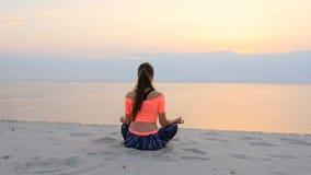 A mulher bonita saudável, nova que medita, ioga praticando na praia, pelo mar, no nascer do sol, relaxa os músculos, mente vídeos de arquivo