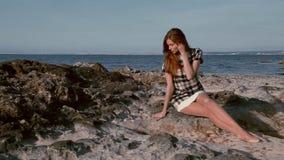 A mulher bonita senta o oceano litoral das pedras filme