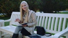A mulher bonita senta-se no banco no parque do outono, faz anotações em um caderno filme