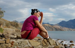 A mulher bonita senta-se no litoral e olha-se longe Imagem de Stock