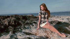 A mulher bonita senta-se no oceanfront das rochas filme