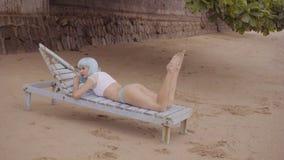 A mulher bonita 'sexy' no estilo futurista moderno que levanta no azul de madeira danificado sunbed Imagens de Stock