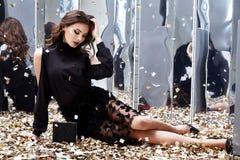 A mulher bonita 'sexy' senta o assoalho com lote do encanto dourado f das lantejoulas foto de stock