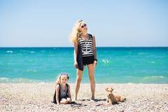 A mulher bonita, sua filha encantador e o terrier perseguem o descanso na praia foto de stock