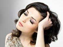 A mulher bonita toca em seus cabelos encaracolado marrons Imagens de Stock Royalty Free