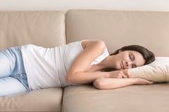 A mulher bonita toma a sesta curto durante o dia no sofá fotos de stock royalty free