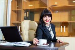 A mulher bonita toma uma xícara de café em uma tabela Fotos de Stock Royalty Free