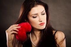 A mulher bonita triste guarda o coração vermelho no preto Fotografia de Stock Royalty Free