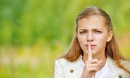 A mulher bonita triste põe o dedo a seus bordos Imagem de Stock
