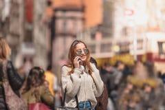 A mulher bonita usa o smartphone ao andar fotografia de stock