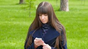 A mulher bonita usa o smartphone da pilha fora no parque - detalhe A menina feliz atrativa nova relaxa em uma paridade da cidade video estoque