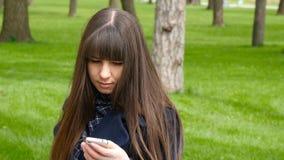 A mulher bonita usa o smartphone da pilha fora no parque - detalhe A menina feliz atrativa nova relaxa em uma paridade da cidade vídeos de arquivo