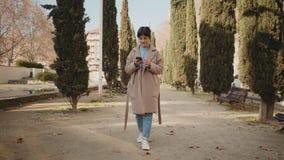 A mulher bonita usa o smartphone no parque filme
