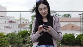 A mulher bonita usa um smartphone vídeos de arquivo