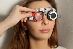 A mulher bonita verifica a visão em um oftalmologista com o corretivo Fotos de Stock Royalty Free