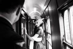 A mulher bonita vestiu-se no vestido vermelho do chá do vintage do chá no trem locomotivo fotos de stock royalty free