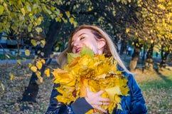 A mulher bonito alegre nova da menina que joga com amarelo caído do outono sae no parque perto da árvore, rindo e sorrindo Imagens de Stock Royalty Free