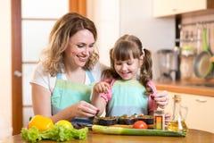 Mulher bonito com a filha da criança que prepara peixes dentro Imagens de Stock Royalty Free
