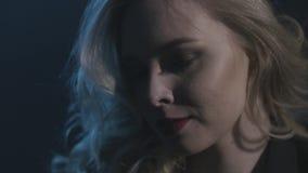 Mulher bonito com o cabelo encaracolado louro que olha de lado no fundo escuro a??o Menina loura nova bonita com longo ondulado video estoque