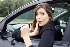 Mulher bonito com o carro novo que olha surpreendido e feliz Foto de Stock
