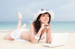 Mulher bonito com o portátil na praia do verão Imagens de Stock