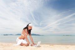 Mulher bonito com o portátil na praia do verão Fotografia de Stock