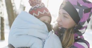 Mulher bonito com um rapaz pequeno que tem o divertimento junto fora no inverno filme