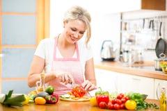 A mulher bonito corta a paprika para a salada imagem de stock royalty free