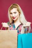 A mulher bonito na camisa colorida está apreciando a compra Retrato de louro surpreendente com os dois sacos de papel no estúdio  Fotos de Stock