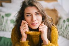 Mulher bonito na camiseta morna que sorri à câmera em casa fotos de stock